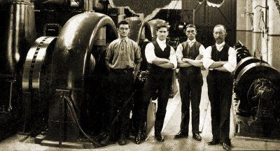 NMETL power station crew next to generator set. Photograph TMSV archive.